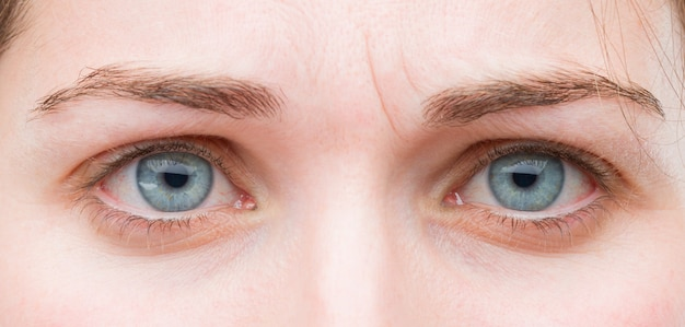 De jonge mooie vrouwen blauwe ogen sluiten omhoog. droevige uitdrukking