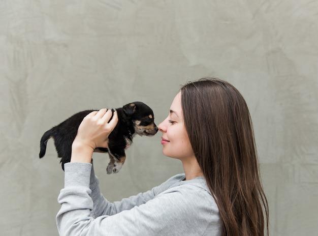 De jonge mooie vrouwen met een klein schattig puppy.