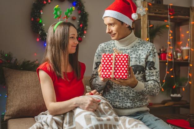 De jonge mooie vrouwenvrouw geeft haar echtgenoot een doos van de verrassingsgift