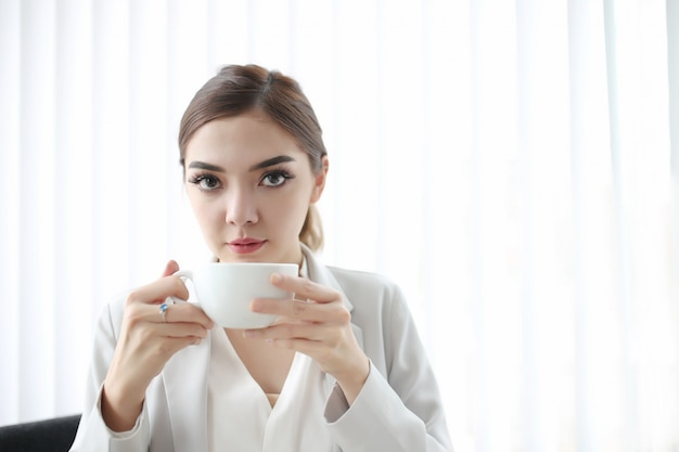 De jonge mooie vrouwenzitting op kantoor drinkt hete koffiekop