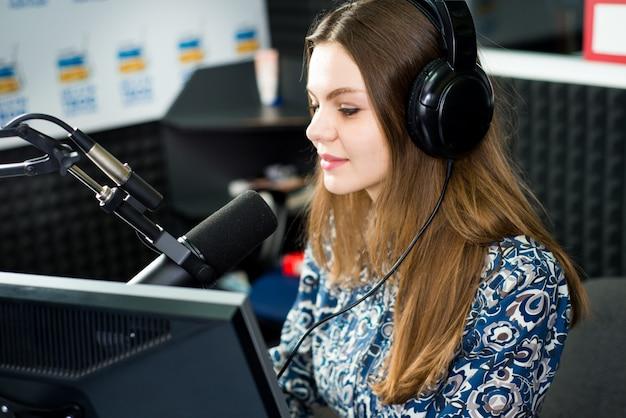 De jonge mooie zitting van de vrouwen radiopresentator in studio met hoofdtelefoons en het spreken op de lucht