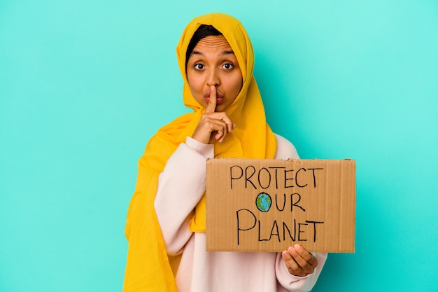 De jonge moslimvrouw die beschermt onze planeet op blauw houdt een geheim houdt of om stilte vraagt.