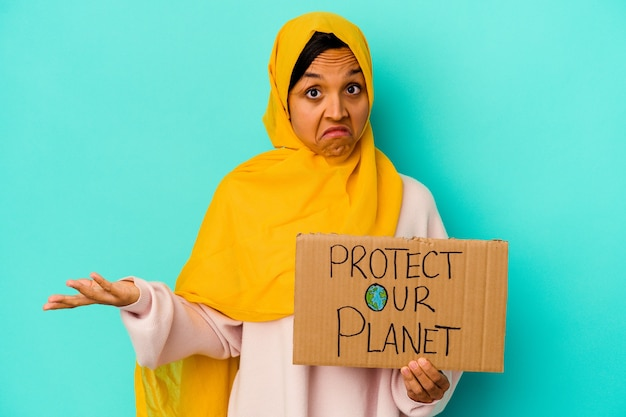 De jonge moslimvrouw die beschermt onze planeet op blauw houdt, haalt schouders op en opent verwarde ogen.