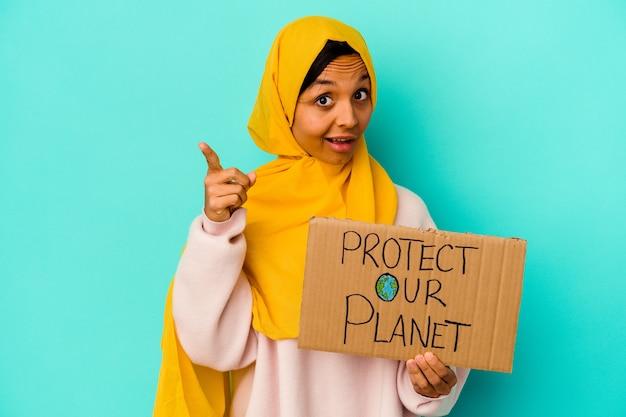 De jonge moslimvrouw die houdt beschermt onze planeet die op blauwe muur wordt geïsoleerd die een idee heeft