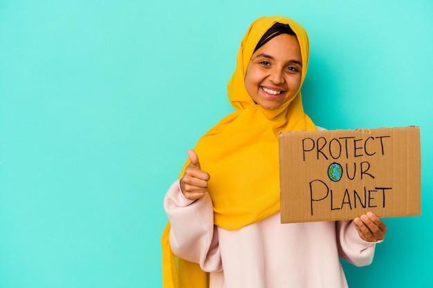 De jonge moslimvrouw die houdt beschermt onze planeet die op blauwe muur wordt geïsoleerd die en duim glimlacht opheft