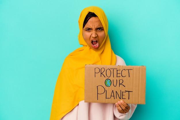 De jonge moslimvrouw die houdt beschermt onze planeet die op blauwe muur wordt geïsoleerd die zeer boos en agressief gilt
