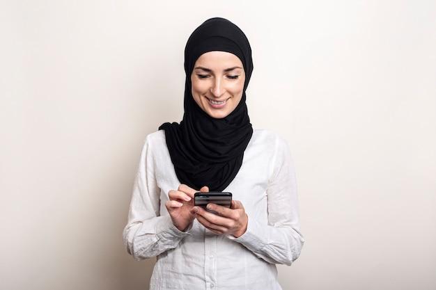 De jonge moslimvrouw in hijab houdt een telefoon in haar handen en glimlacht