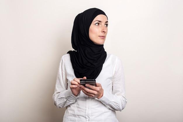 De jonge moslimvrouw in hijab houdt een telefoon in haar handen en kijkt naar de zijkant