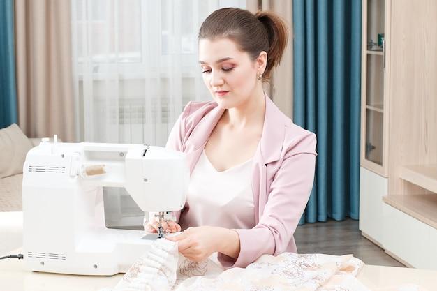 De jonge naaistervrouw naait kleren op naaimachine.