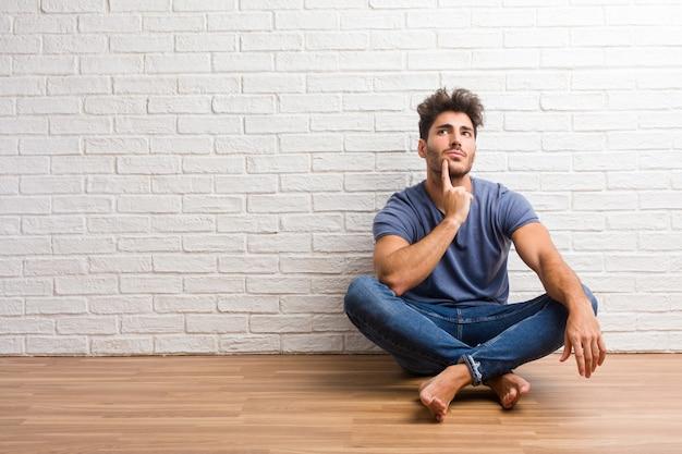 De jonge natuurlijke mens zit op een houten en vloer die omhoog denken, verward over een idee kijken