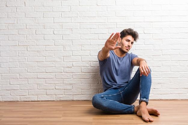 De jonge natuurlijke mens zit op een houten ernstige en bepaalde vloer, stak hand in voorzijde, houdt gebaar tegen, ontkent concept