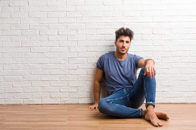 De jonge natuurlijke mens zit op een houten vloer vrolijk en met een grote zekere glimlach,