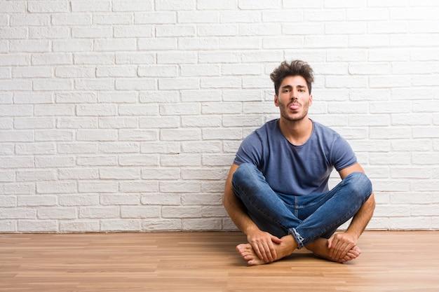 De jonge natuurlijke mens zit op een houten vloeruitdrukking van vertrouwen en emotie