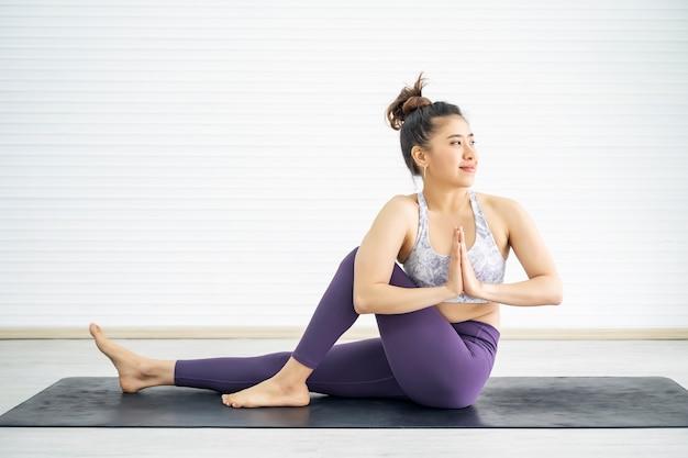 De jonge oefening van de sportvrouw met yoga thuis
