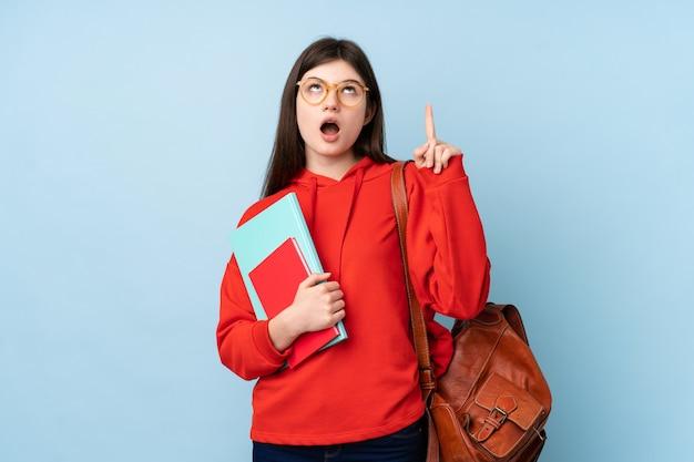 De jonge oekraïense vrouw die van de tienerstudent een salade over geïsoleerde blauwe muur houden die met de wijsvinger een groot idee richten