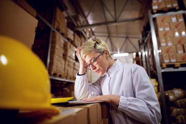 De jonge ongerust gemaakte toegewijde vrouwelijke werknemer in faciliteitsopslaggebied controleert document vellen die op een stapel dozen in fabrieksopslagruimte worden geleund.