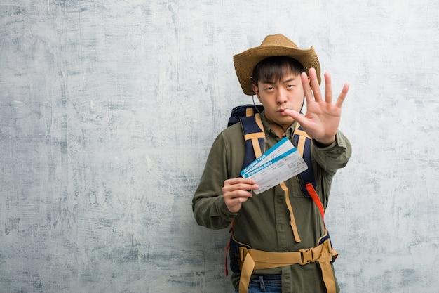 De jonge ontdekkingsreiziger chinese mens die luchtkaartjes het zetten houden dient voorzijde in
