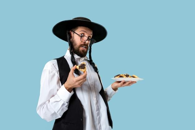De jonge orthodox-joodse man met zwarte hoed met hamantaschen-koekjes voor het joodse festival van purim