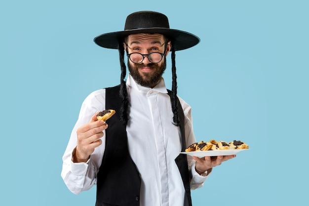 De jonge orthodoxe joodse man met hamantaschenkoekjes voor festival purim. vakantie, viering, jodendom, gebak, traditie, koekje, religieconcept