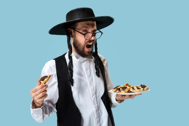 De jonge orthodoxe joodse man met hamantaschenkoekjes voor festival purim