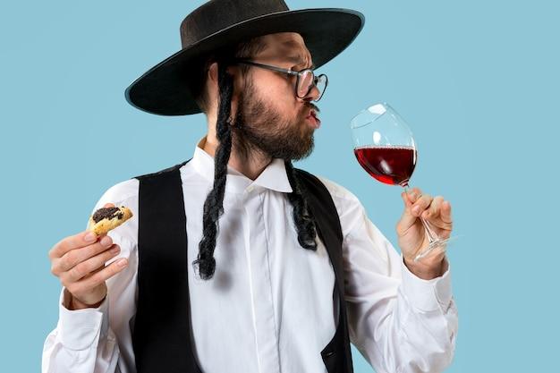 De jonge orthodoxe joodse man met hamantaschenkoekjes voor festival