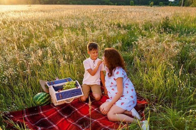 De jonge ouders en hun zoon picknicken op het tarweveld op een zonnige dag. de zoon speelt gitaar voor zijn ouders. zwangere familiefotoshoot in de natuur