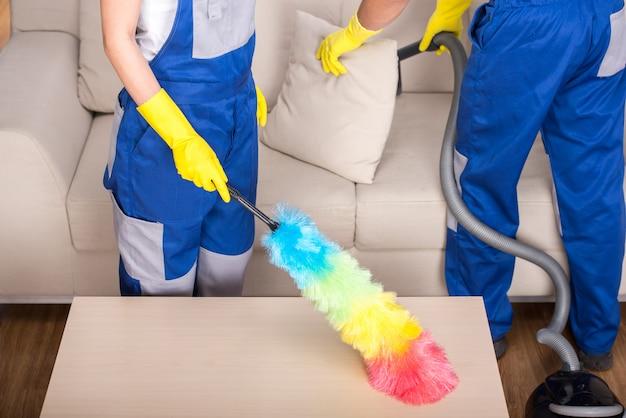 De jonge paar professionele schoonmakers maken het huis schoon.