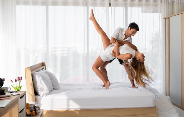 De jonge paarminnaar geniet van dansend samen in slaapkamer