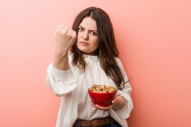 De jonge plus grootte bochtige vrouw die een graangewassen houdt werpt het tonen van vuist aan camera, agressieve gelaatsuitdrukking.