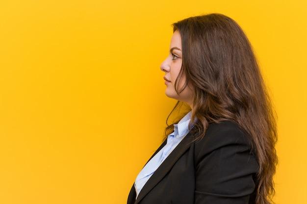 De jonge plus grootte kaukasische bedrijfsvrouw die links, zijwaarts staart staart stelt.
