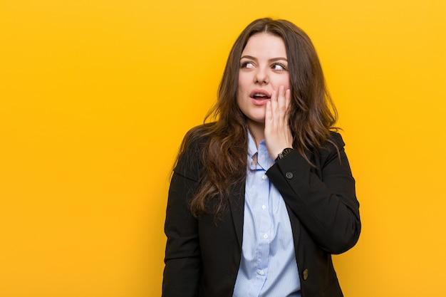 De jonge plus grootte kaukasische bedrijfsvrouw zegt een geheim heet remmend nieuws en opzij kijkend