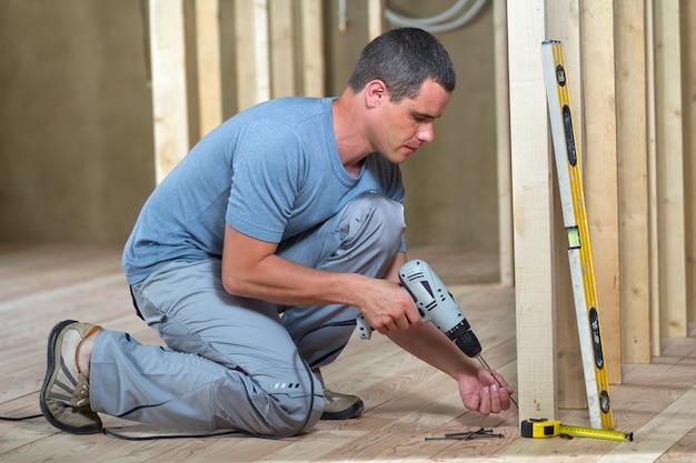 De jonge professionele arbeider gebruikt niveau en schroevedraaier die houten frame installeren voor toekomstige muren. interieur van zolderkamer met eiken vloer onder wederopbouw. renovatie en verbetering concept.