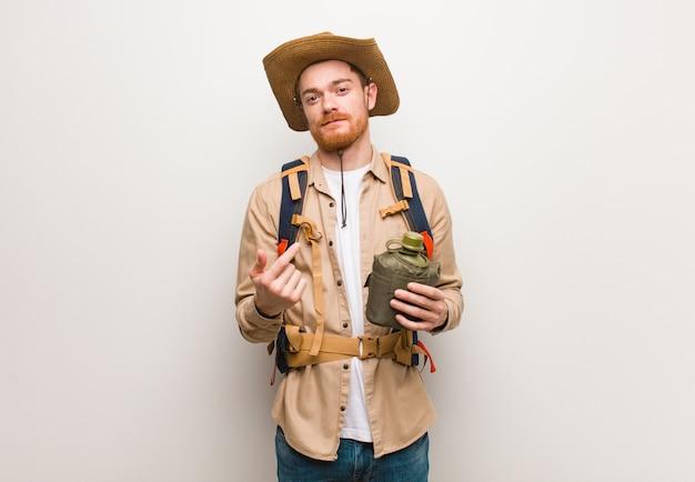 De jonge redhead ontdekkingsreizigermens die uitnodigen te komen. hij houdt een veldfles vast.