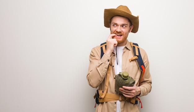 De jonge redhead ontdekkingsreizigermens ontspande het denken over iets bekijkend een exemplaarruimte. hij houdt een veldfles vast.