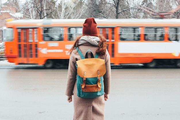 De jonge reiziger van het vrouwen krullende rode hoofdmeisje met rugzak voor tram bij de stadsstraat