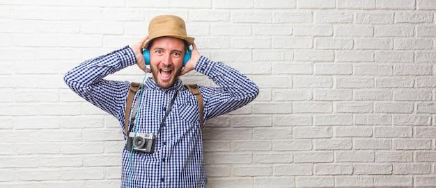 De jonge reizigersmens die rugzak en een uitstekende verrast en geschokte camera dragen, kijkend met wijd open ogen, opgewekt door een aanbieding of door een nieuwe baan, wint concept.