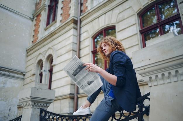De jonge roodachtige krant van de mensenlezing dichtbij de oude stijlbouw