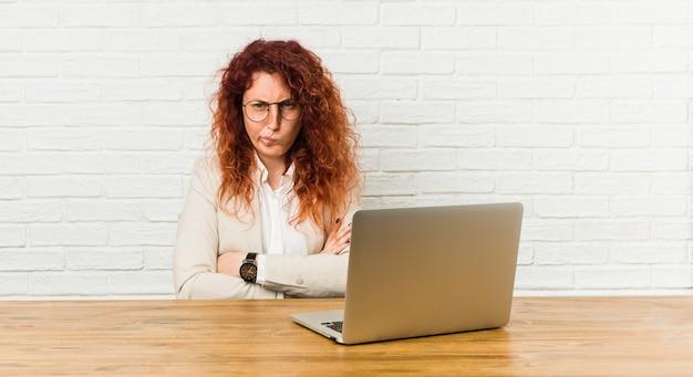 De jonge roodharige krullende vrouw die met haar laptop het fronsen gezicht in ongenoegen werkt, houdt wapens gevouwen.