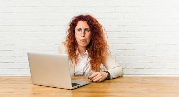 De jonge roodharige krullende vrouw die met haar laptop werkt haalt schouders op en verwarde ogen.