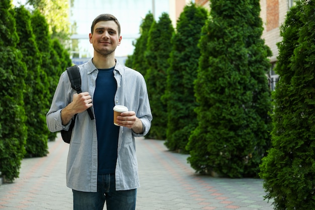 De jonge rugzak van de studentengreep en kop van koffie. studie. universiteit