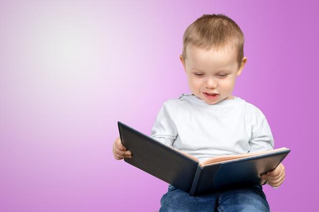 De jonge schooljongen houdt een blauw boek
