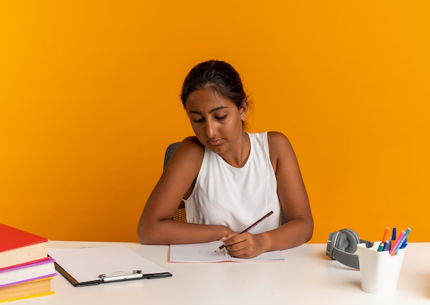 De jonge schoolmeisjeszitting aan bureau met schoolhulpmiddelen schrijft iets op notitieboekje op oranje