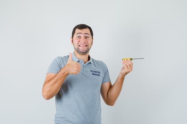 De jonge schroevendraaier van de technicusholding, die duim in grijs uniform toont en vreugdevol kijkt.