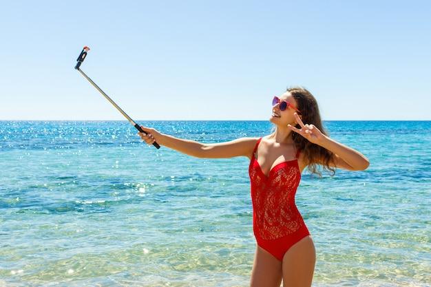 De jonge sexy vrouw gekleed in manierzwempak die mobiele telefooncamera met behulp van voor neemt selfie
