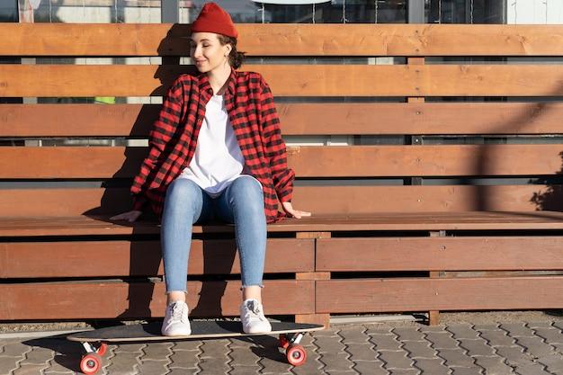 De jonge skateboarder van het hipstermeisje geniet van zonlicht en zit op een houten bank met de voeten op een longboard glimlachend