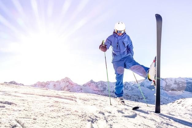 De jonge skiër op blauwe eenvormig bij zonsondergang ontspant ogenblik in franse de skitoevlucht van alpen