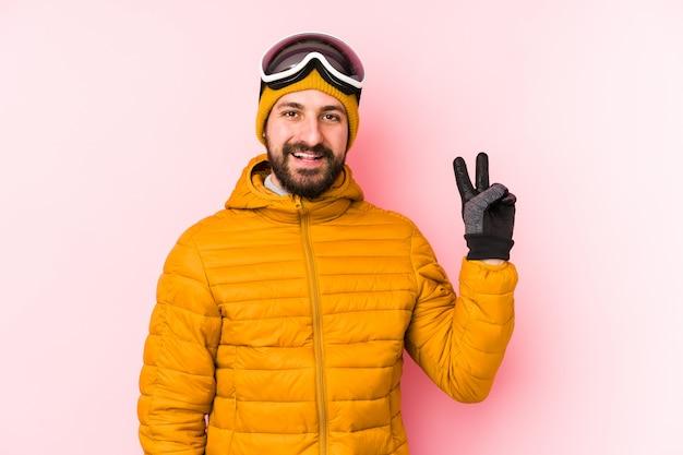 De jonge skiërmens isoleerde blij en onbezorgd tonend een vredessymbool met vingers.