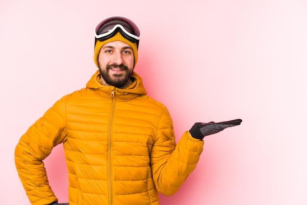 De jonge skiërmens isoleerde het tonen van een exemplaarruimte op een palm en het houden van een andere hand op taille.