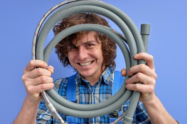 De jonge slang van de loodgieterholding van gootsteen in handen