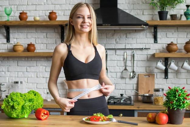 De jonge slanke vrouw meet taille, houdt de vrouw zich aan dieet